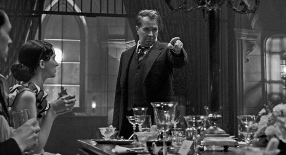 Gary Oldman como Mank en una fiesta de Hearst.